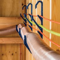 The Dust Right® Cord and Hose Hooks holding three cords and a hose traveling along a wall