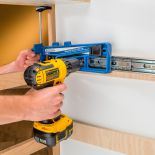 Man using the Rockler Universal Drawer Slide Jig to screw a slide to the wall
