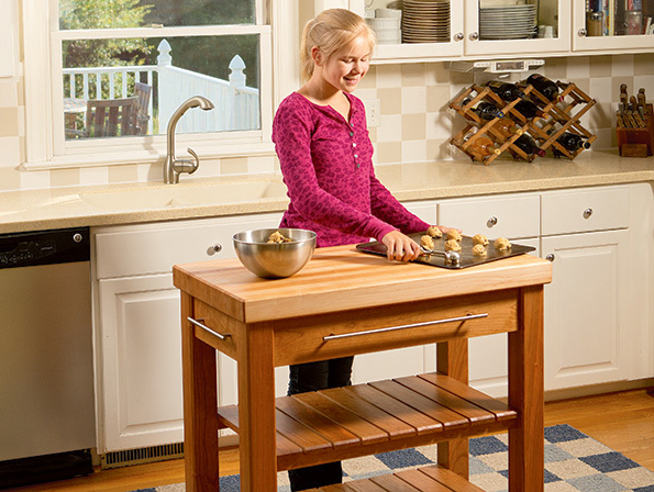 girl making cookies behind kitchen island