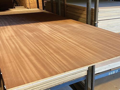 Stack of mahogany plywood panels on a lumberyard shelf