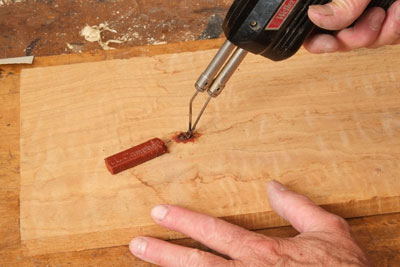 Using a burn-in stick to fill a blemish in wood