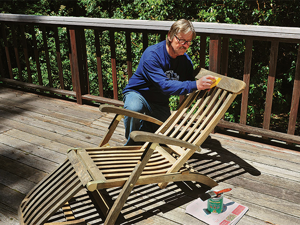 Wiping spar varnish on a deck chair