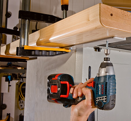Screwing outfeed table mounting plate to cabinet saw fence railing