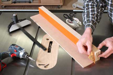 Attaching sandpaper strip to fence with double-sided tape