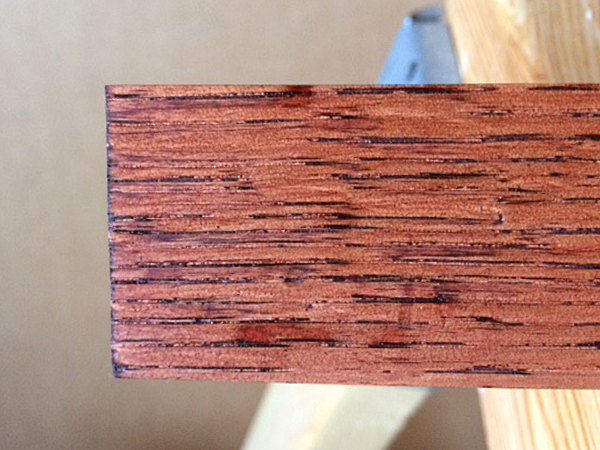 Stain bleeding into the pores of a piece of red oak lumber