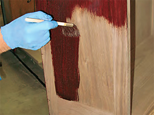 Applying a layer of stain on the side of a bureau