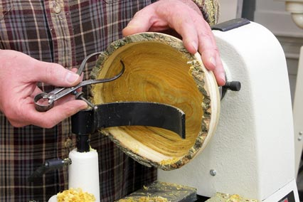 Using a calipers to check the interior thickness of a natural edge bowl blank