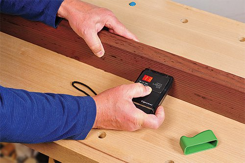 Checking the moisture content of a piece of outdoor furniture with a moisture meter