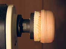 Cherry blank glued to sacrificial pine base on a faceplate for bowl turning
