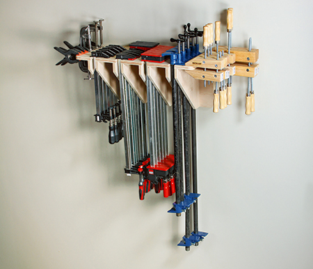 Clamp storage rack with forty clamps on a workshop wall