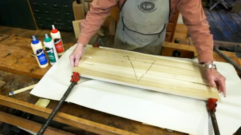 Using bar clamps to glue wood pieces into a panel