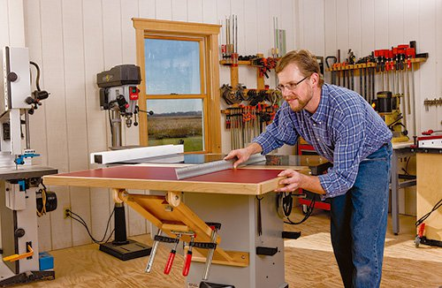 Clamping outfeed table to cabinet saw and measuring the levelness