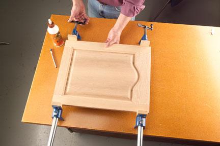 Applying pressure to door panel with bar clamps