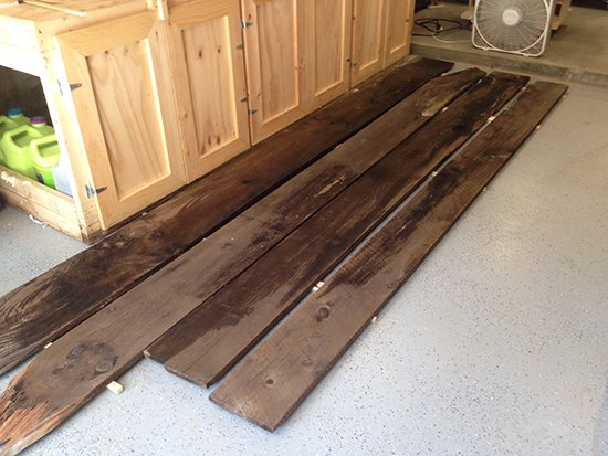 Laying out antique wood planks on a shop floor for color and grain matching