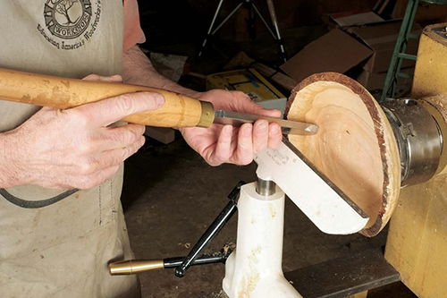 Using a dome scraper to carve out a bowl interior