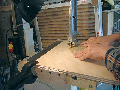Using a circle cutting jig to rotate a panel along a band saw
