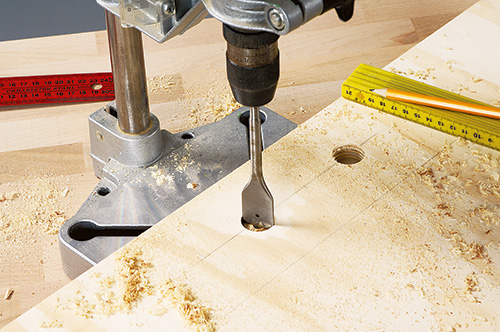 Boring holes in coffee table bed base with a drill press