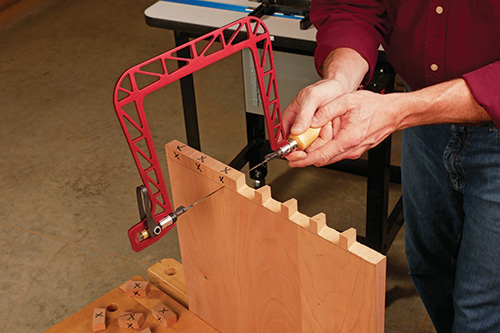 Using a coping saw to cut waste from tail sockets of dovetail joint