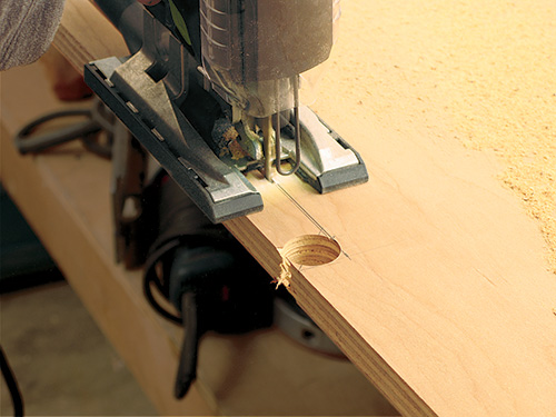 Using a jigsaw to cut holes for wires in media console