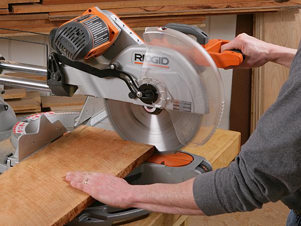 Pushing a sliding miter saw cut through a board