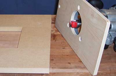 Router attached to a plywood template to guide router cut