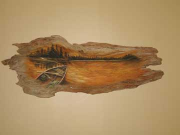 A piece of driftwood with a river canoeing scene painted on it