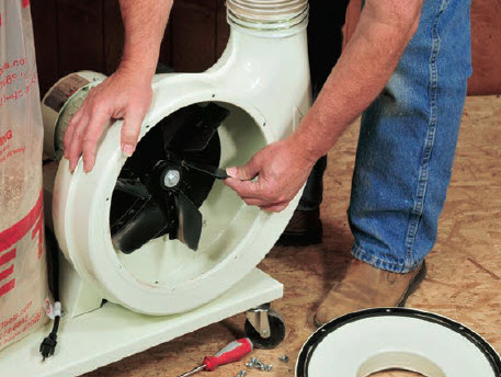 man checking the fans of a dust collector