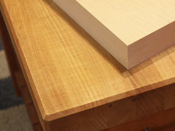 A maple countertop with stain applied and an unfinished piece