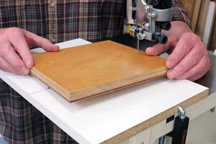 Setting workpiece on dowel in band saw cutting jig