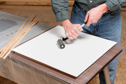 Using j-roller to flatten an even out adhesive under plastic laminate