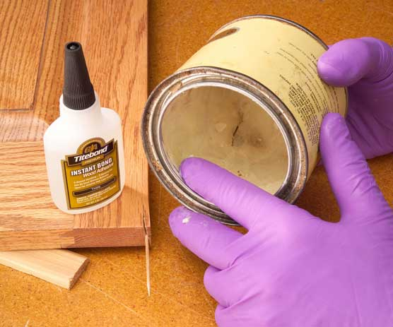 Scooping paste wax with a gloved finger