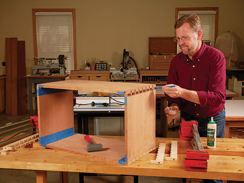 Applying glue to dovetail joint and clamping the finished joinery