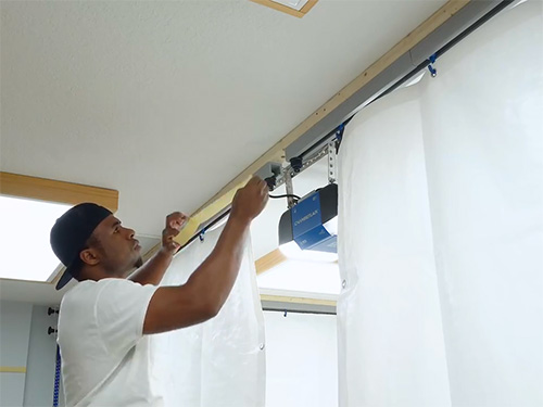 Hanging tarp from ceiling track for painting booth