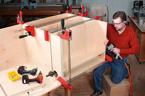 Using brad nails to assemble cabinet base and shelving