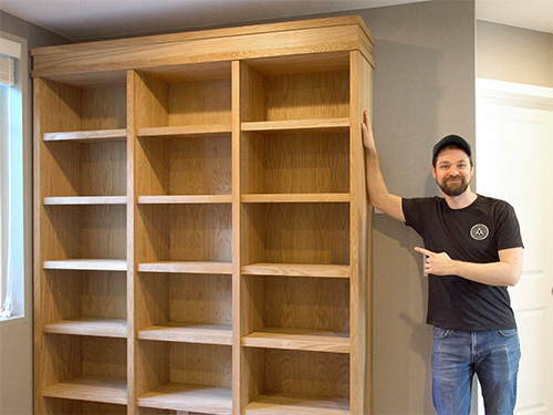 Michael Alm standing with his large display case bookshelf