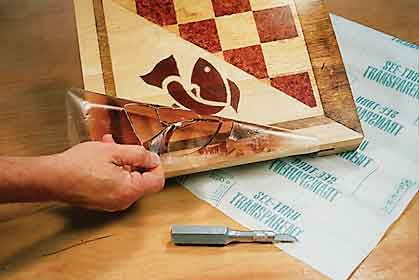 Using a transparent sheet to create patterned stain