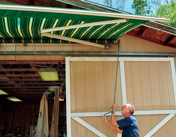 Setting up large awning over workshop door