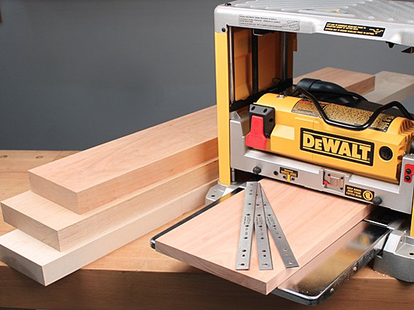 A portable planer with planed lumber and extra blades