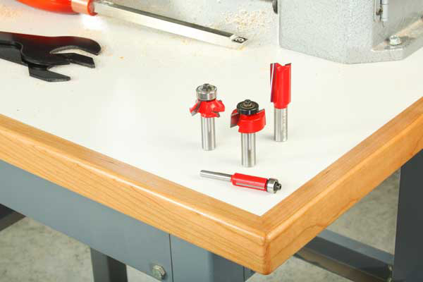 Workshop table with laminate top and four router bits