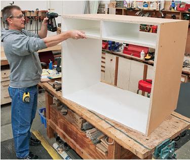 man assembling island casework