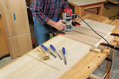 man using handhel wood router