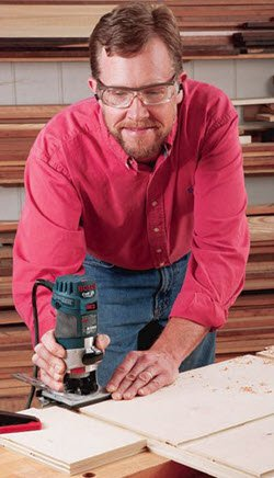 man using trim router to cut joinery