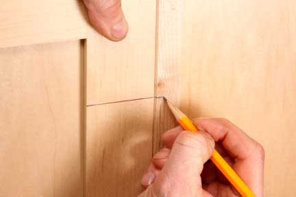 Using a pencil to mark out the location for installing a cabinet hinge