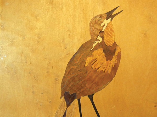 Image of a bird created in wood with marquetry inlays