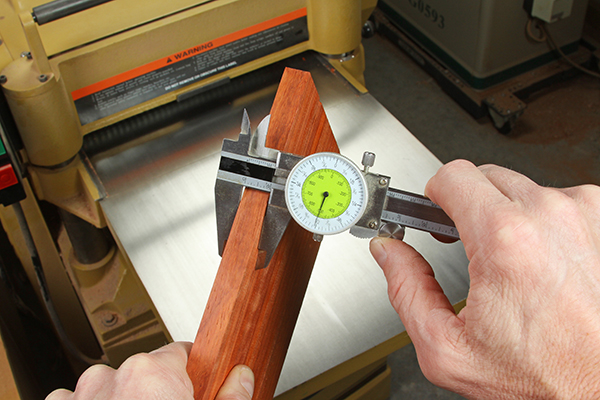 Using a caliper to check the thickness of stock for cutting dowels