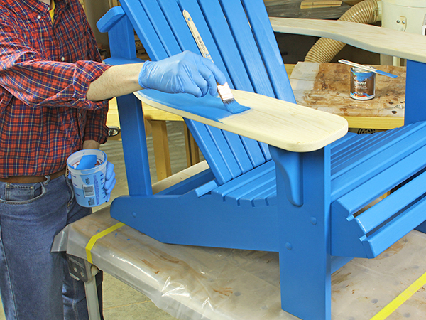 Applying blue paint onto an adirondack chair