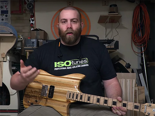 Paul Jackman with a guitar made from recycled pallet wood