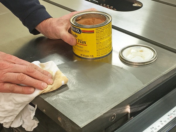 Rubbing a coat of paste wax on a cast iron table saw top