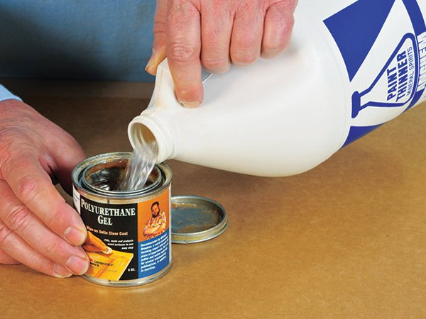 Pouring a layer of paint thinner into a can of polyurethane gel