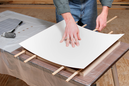 Pressing laminate sheet over panel